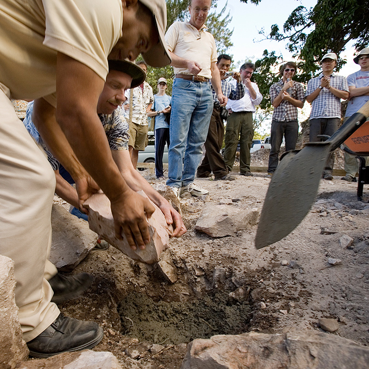 People digging and removing stones from a hole in the ground