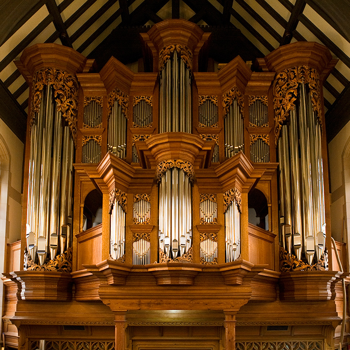 Baroque organ pipes amidst fancy wooden scrollwork
